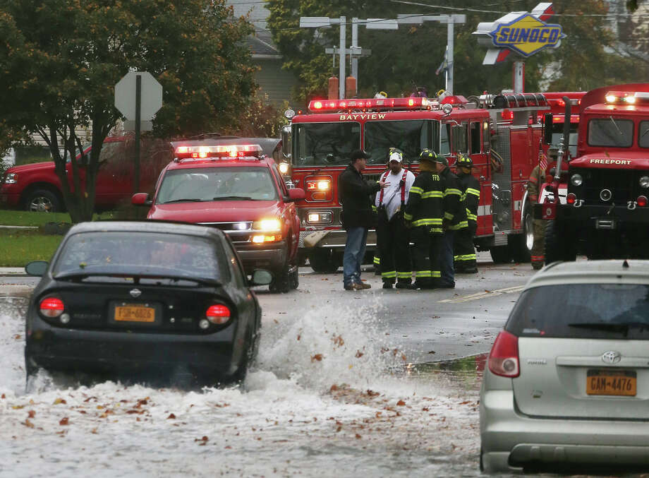 Members of  the Bayview Hose Company No. 3 of the Freeport Fire Department survey the situation on South Long Beach Avenue as high tide and winds from Hurricane Sandy combine to flood the area on October 29, 2012 in Freeport, New York. The storm, which threatens 50 million people in the eastern third of the U.S., is expected to bring days of rain, high winds and possibly heavy snow. Photo: Bruce Bennett, Getty Images / 2012 Getty Images