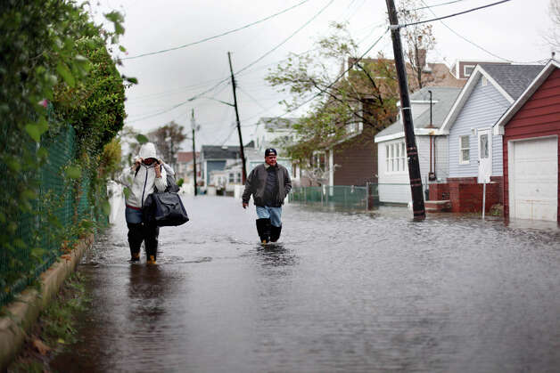 People wade through flood water in Broad Channel as Hurricane Sandy begins to affect the area on October 29, 2012 in the Queens borough of New York City. The storm, which threatens 50 million people in the eastern third of the U.S., is expected to bring days of rain, high winds and possibly heavy snow. New York Governor Andrew Cuomo announced the closure of all New York City's bus, subway and commuter rail service as of Sunday evening. Photo: Allison Joyce, Getty Images / 2012 Getty Images
