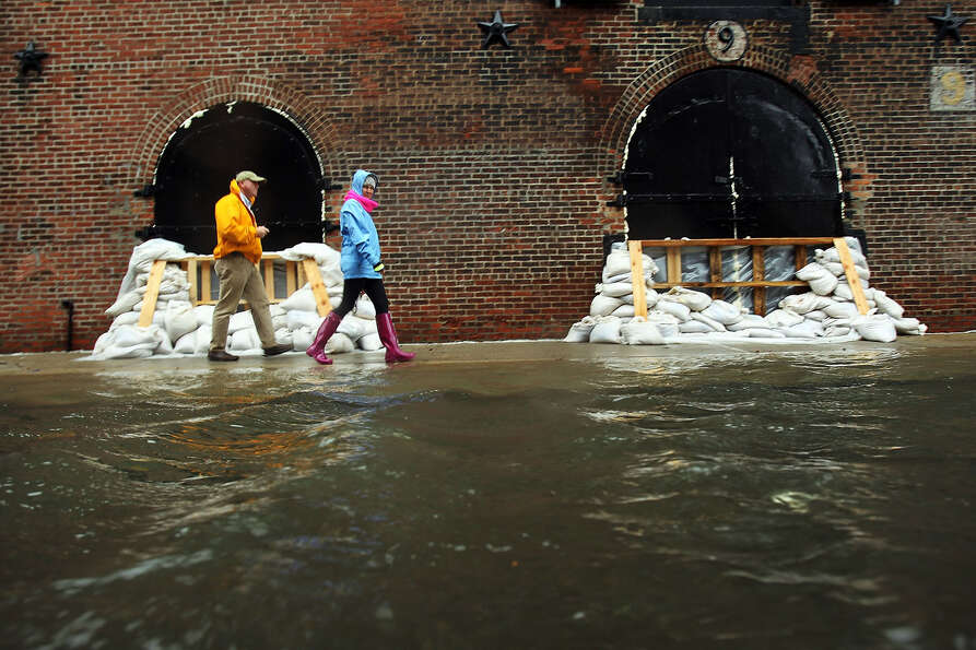 People walk past sandbags on a flooded street as Hurricane Sandy moves closer to the area on Octob