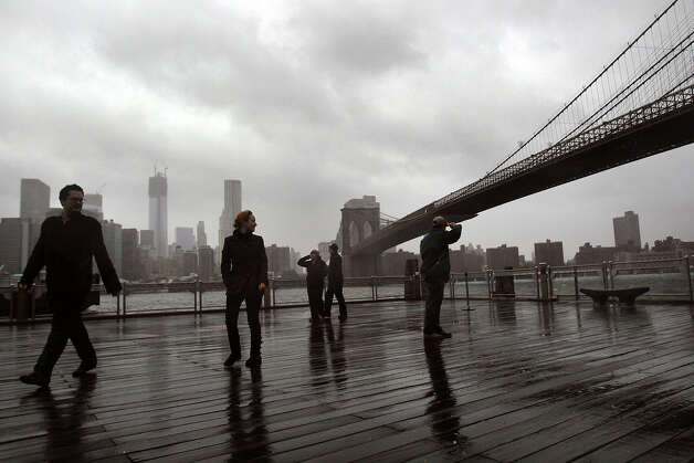 People look out at the Brooklyn Bridge October 29, 2012 in the Brooklyn borough of New York City. The storm, which threatens 50 million people in the eastern third of the U.S., is expected to bring days of rain, high winds and possibly heavy snow. New York Governor Andrew Cuomo announced the closure of all New York City will  bus, subway and commuter rail service as of Sunday evening. Photo: Spencer Platt, Getty Images / 2012 Getty Images
