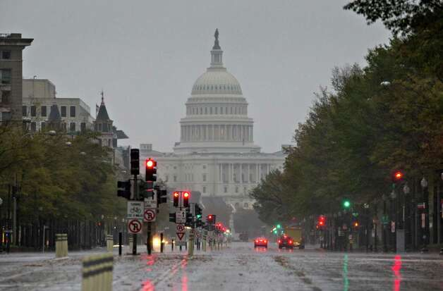 The U.S. Capitol and Pennsylvania Avenue are seen Monday morning, Oct. 29, 2012, as heavy rain from Hurricane Sandy arrives in Washington. Sandy strengthened before dawn and is on a predicted path toward Washington, Baltimore, Philadelphia and New York — putting it on a collision course with two other weather systems that would create a superstorm.  (AP Photo/J. Scott Applewhite) Photo: J. Scott Applewhite, Associated Press / AP