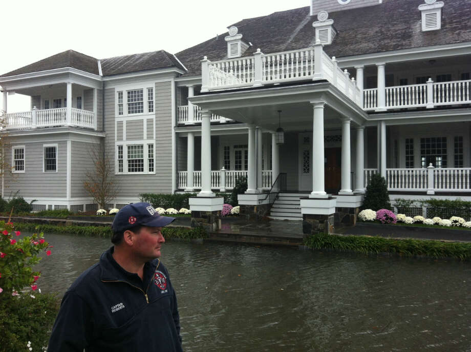 Larry Roberts, deputy chief of training and a safety officer with the Greenwich Fire Department, surveys the storm surge from Hurricane Sandy outside the Belle Haven Club just after high tide Monday, Oct. 29, 2012.