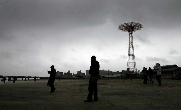 People brave high winds and blowing sand as they walk on Coney Island beach in the Brooklyn borough of New York as Hurricane Sandy arrives, Monday, Oct. 29, 2012.  Hurricane Sandy continued on its path Monday, as the storm forced the shutdown of mass transit, schools and financial markets, sending coastal residents fleeing, and threatening a dangerous mix of high winds and soaking rain. (AP Photo/Mark Lennihan) Photo: Mark Lennihan, Associated Press / AP