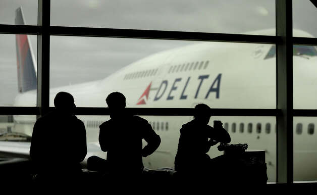 Travelers on Delta Airlines waits for flights Monday, Oct. 29, 2012, in Detroit. Dozens of departing flights have been canceled at Detroit Metropolitan Wayne County Airport as a looming superstorm locks down flights to the East Coast. Hurricane Sandy continued on its path Monday, as the storm forced the shutdown of mass transit, schools and financial markets, sending coastal residents fleeing, and threatening a dangerous mix of high winds and soaking rain.  Photo: Charlie Riedel, AP / AP2012