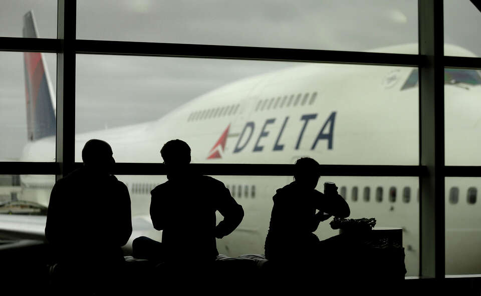Travelers on Delta Airlines waits for flights Monday, Oct. 29, 2012, in Detroit. Dozens of departing
