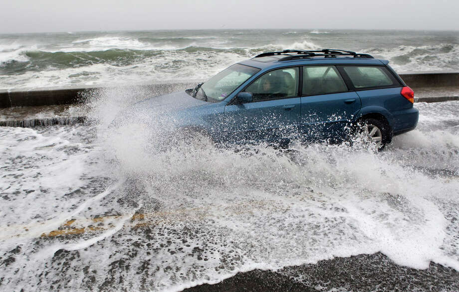 A motorist drives through a flooded road along the Atlantic Ocean during the early stages of Hurricane Sandy, Monday, Oct. 29, 2012, in Kennebunk, Maine. The hurricane continued on its path Monday, as the storm forced the shutdown of mass transit, schools and financial markets, sending coastal residents fleeing, and threatening a dangerous mix of high winds and soaking rain. Photo: Robert F. Bukaty, AP / AP
