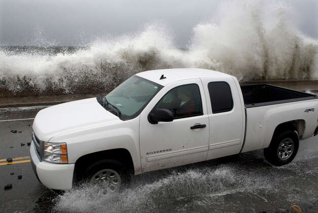 A motorist tries to avoid getting hit by a large wave as it crashes over a seawall on the Atlantic Ocean during the early stages of Hurricane Sandy, Monday, Oct. 29, 2012, in Kennebunk, Maine. The hurricane continued on its path Monday, as the storm forced the shutdown of mass transit, schools and financial markets, sending coastal residents fleeing, and threatening a dangerous mix of high winds and soaking rain. Photo: Robert F. Bukaty, AP / AP