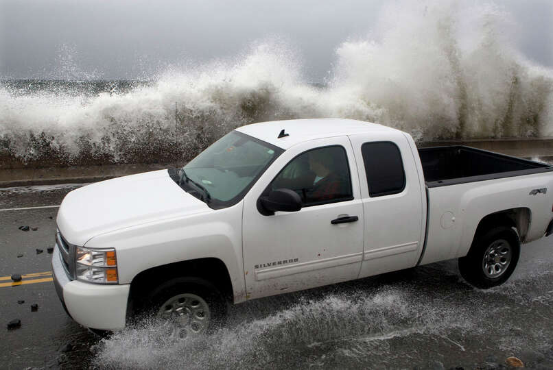 A motorist tries to avoid getting hit by a large wave as it crashes over a seawall on the Atlantic O