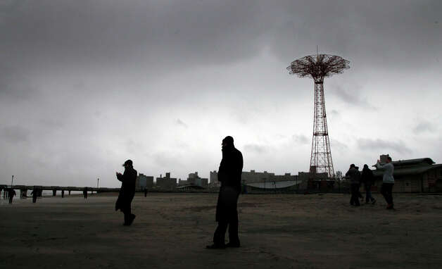 People brave high winds and blowing sand as they walk on Coney Island beach in the Brooklyn borough of New York as Hurricane Sandy arrives, Monday, Oct. 29, 2012.  Hurricane Sandy continued on its path Monday, as the storm forced the shutdown of mass transit, schools and financial markets, sending coastal residents fleeing, and threatening a dangerous mix of high winds and soaking rain. Photo: Mark Lennihan, AP / AP2012