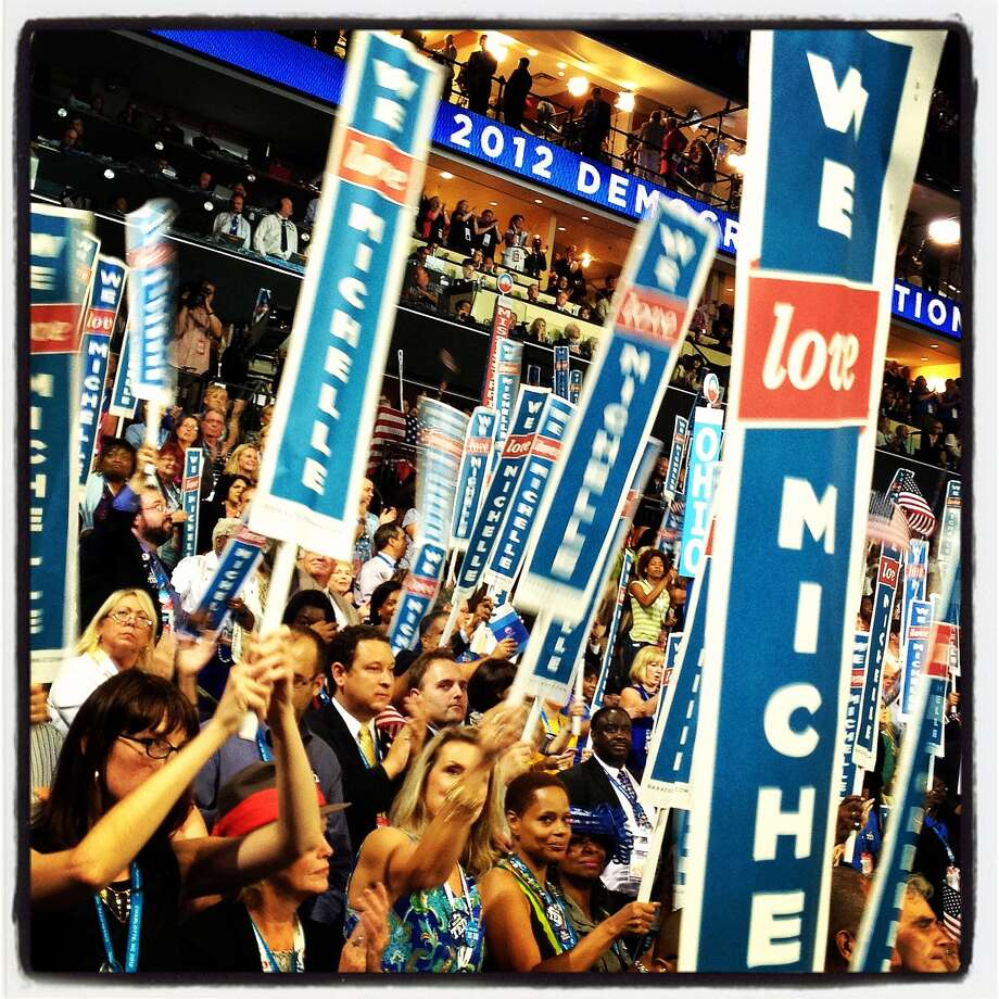 People hold first lady Michelle Obama signs during the Democratic National Convention (DNC) at Time Warner Cable Arena September 4, 2012 in Charlotte, North Carolina. The Democratic National Convention is scheduled to start on Tuesday and run through September 6th. Photo: Justin Sullivan, Getty Images / 2012 Getty Images