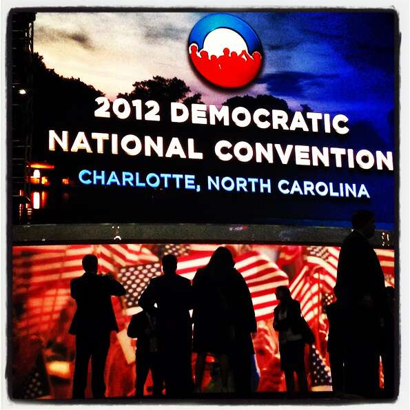 People stand in front of screens at the end of the third day of the Democratic National Convention a