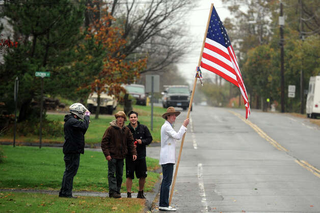 Patrick Spada holds an American Flag as he stands with friend on Oak Bluff Ave., in the Lordship section of Stratford, Conn. Oct. 29th, 2012. Photo: Ned Gerard