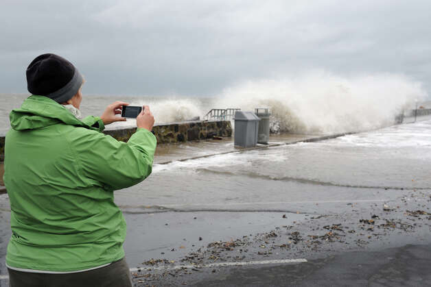 Ellie McAuliffe takes a photograph as waves break over the sea wall along Beach Drive, in the Lordship section of Stratford, Conn. Oct. 29th, 2012. Photo: Ned Gerard / Connecticut Post