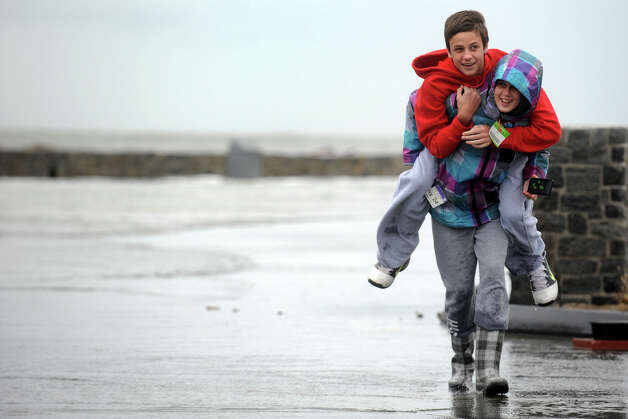 Stephanie DiCostanzo carries her brother Matt as water floods Beach Drive, in the Lordship section of Stratford, Conn. Oct. 29th, 2012. Photo: Ned Gerard