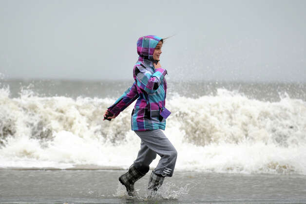 Stephanie DiCostanzo runs through flood water as waves break over the sea wall along Beach Drive, in the Lordship section of Stratford, Conn. Oct. 29th, 2012. Photo: Ned Gerard