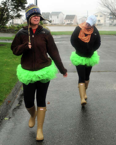 Bree and Bridget Murphy walk in the rain near their home on 4th Ave. in the Lordship section of Stratford, Conn. Oct. 29th, 2012. The twin sisters were wearing tutus they bought for halloween. Photo: Ned Gerard
