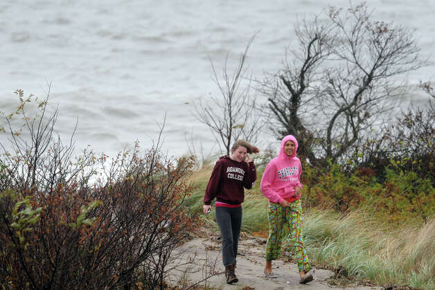 Payton Barta and Kheyenne Young walk through the dunes after watching waves on Long Island Sound in the Lordship section of Stratford, Conn. Oct. 29th, 2012. Photo: Ned Gerard