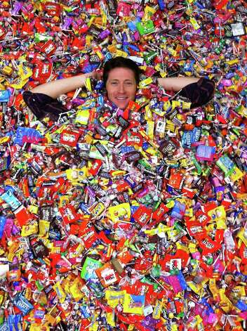 Orthodontist Tito Norris poses with the candy his office collected last year through a Halloween candy buyback program. Photo: Stone Oak Orthodontics