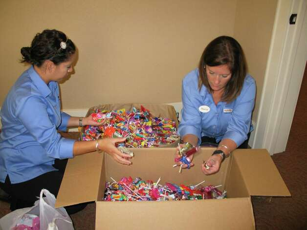 Kyla Klemme, left, and Maria Hardt from Dr. Richard Hulme's office sort candy to make sure wrappers are intact. Photo: Courtesy Photo