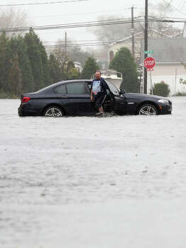 LINDENHURST, NY - OCTOBER 29: Joseph Arpaio of Massapequa abondons his car on 5th Street in Lindenhurst as high tide, rain and winds flood local streets on October 29, 2012 in Lindenhurst, New York.The storm, which threatens 50 million people in the eastern third of the U.S., is expected to bring days of rain, high winds and possibly heavy snow. Photo: Bruce Bennett, Getty Images / 2012 Getty Images