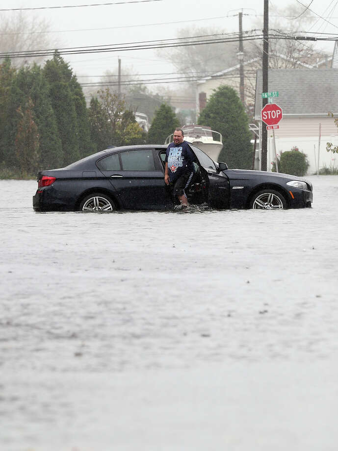 Joseph Arpaio of Massapequa abondons his car on 5th Street in Lindenhurst as high tide, rain and winds flood local streets on October 29, 2012 in Lindenhurst, New York.The storm, which threatens 50 million people in the eastern third of the U.S., is expected to bring days of rain, high winds and possibly heavy snow. Photo: Bruce Bennett, Getty Images / 2012 Getty Images