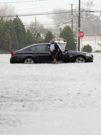 Joseph Arpaio of Massapequa abondons his car on 5th Street in Lindenhurst as high tide, rain and win