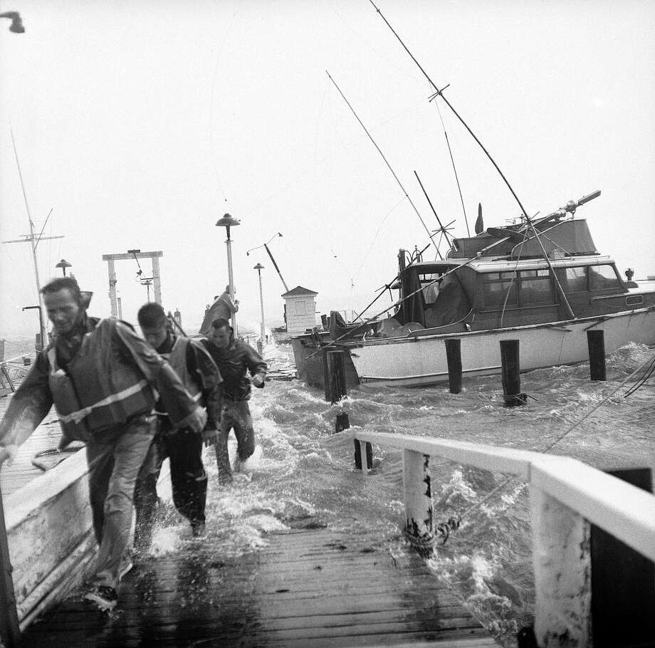 Raging seas whipped up by Hurricane Carol drive fishing boat crewmen back along the partially submerged dock of the Montauk Yacht Club in Montauk, Long Island, New York, during attempts to secure boats torn loose from their moorings, Aug. 31, 1954. The driving storm caused widespread damage in this fishing and resort area on Long Island?s eastern tip before smashing into southern New England. Photo: AP