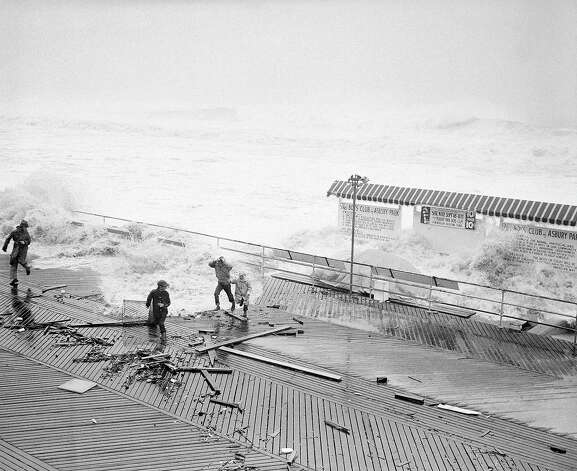 High waves roll in over the beach and crash against the boardwalk at Asbury Park, New Jersey on August 31, 1954, driving these youngsters away from the rail. Canvas-covered auto, on display in connection with a local raffle, is pounded by the surf. A fast-moving hurricane with winds up to 100 miles an hour and torrential rains, swept up the Atlantic coast on August 31, hitting New Jersey and New York before throwing its full fury into New England. Photo: AP