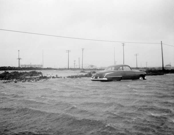 An auto is stranded on Montauk Highway at Napeague, Long Island, New York on August 31, 1954, following Hurricane Carol which caused untold damage on eastern end of the island. In background, left, is radio station WSL, a Mackay radio facility. Framework of the radio tower topped by high winds which reached 90 plus miles per hour in gusts, can be seen at center. At height of storm waves broke narrow waist of Montauk peninsula, channeling through to Napeague bay and making an island of Montauk for a few hours. Photo: AP