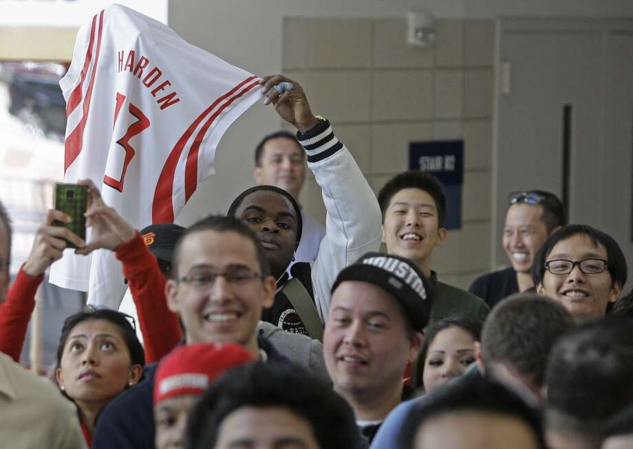 A fan holds up a No. 13 Harden jersey. (Melissa Phillip / Chronicle)
