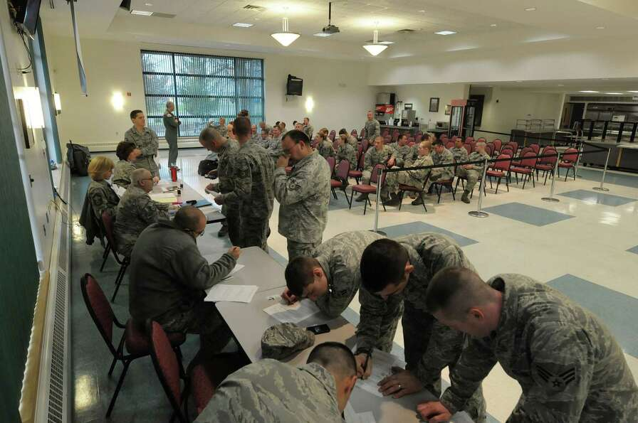 Soldiers fill out paperwork as members of the 109th Airlift Wing, Air National Guard are processed i
