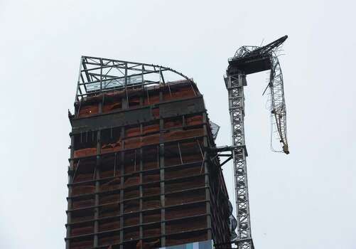 A construction crane atop a luxury high-rise dangles precariously over the streets after collapsing in high winds from Hurricane Sandy, Monday, Oct. 29, 2012, in New York. Hurricane Sandy bore down on the Eastern Seaboard's largest cities Monday, forcing the shutdown of mass transit, schools and financial markets, sending coastal residents fleeing, and threatening a dangerous mix of high winds, soaking rain and a surging wall of water up to 11 feet tall. Photo: John Minchillo / Associated Press