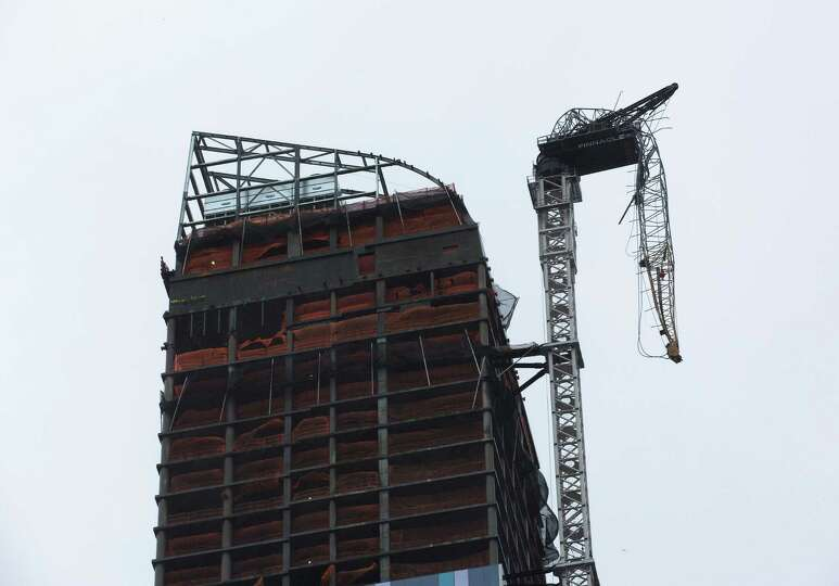 A construction crane atop a luxury high-rise dangles precariously over the streets after collapsing