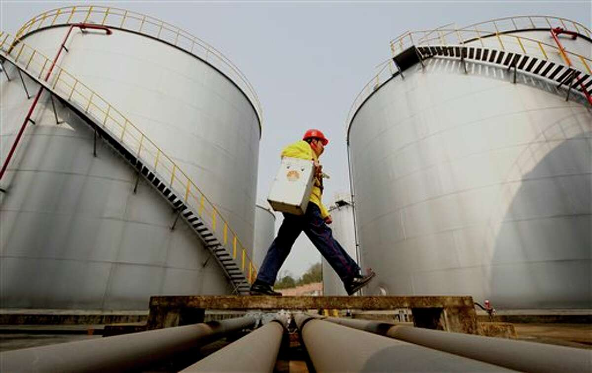 FILE - In this Thursday, Jan. 28, 2010 file photo, a worker walks past tanks at a Petrochina storage base in Suining, in southwest China's Sichuan province. A big shift is happening in Big Oil: an American giant now ranks second to a Chinese upstart. Exxon Mobil is pumping less oil than PetroChina, a company formed just 13 years ago by the Chinese government to better compete for the world's oil and natural gas. On March 29, 2012, the shift is expected to become official when the Beijing company announces that it produced more crude last year than its 130-year-old Texas rival.