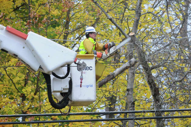 A tree trimming worker uses a chainsaw to remove a tree from a live wire on Krumkill Road on on Monday, Oct. 29, 2012 in Albany, N.Y. (Lori Van Buren / Times Union) Photo: Lori Van Buren