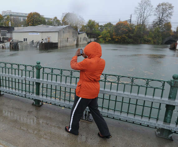 A man on the Mill Street Bridge takes a photo of th Byram River during Hurricane Sandy in Byram, Monday afternoon, Oct. 29, 2012. Photo: Bob Luckey / Greenwich Time