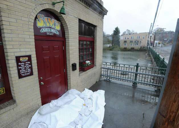 Sandbags block the doorway of Sam's Bar & Grill during Hurricane Sandy in Port Chester, N.Y., Monday afternoon, Oct. 29, 2012. At center of photo is the Byram River in the background is Byram, Connecticut. Photo: Bob Luckey / Greenwich Time