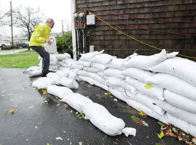 James Noble of Cos Cob reinforces the sandbag wall at his Strickland Road home during Hurricane Sandy, Monday afternoon, Oct. 29, 2012. Noble said the morning high tide came within inches of the wall and that he was expecting a higher tide around midnight. Photo: Bob Luckey / Greenwich Time