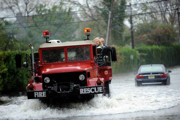 A fire rescue truck from Sound Beach Volunteer Fire Department helps people during the hurricane Sandy on Shore Road in Old Greenwich Monday Oct. 29, 2012.  Behind is a car that is stuck partially underwater. Photo: Helen Neafsey / Greenwich Time