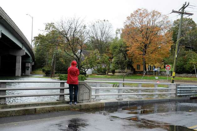 A person watches the water grow from hurricane Sandy on River Road in Cos Cob, Oct. 30. 2012. Photo: Helen Neafsey