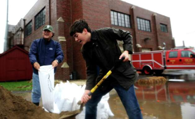 C.J. Jung and his son Malcolm, 15, get bags of dirt to stop the flooding at their home from the Cos Cob Volunteer Fire Company during the hurricane Sandy Monday, Oct. 29, 2012. Photo: Helen Neafsey / Greenwich Time