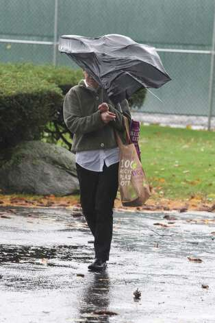 Abby Lane of Greenwich Conn. finds her umbrella broken  as she walked home from the store in harsh rains and wind from Hurricane Sandy on Monday, Oct. 29, 2012. Photo: J. Gregory Raymond
