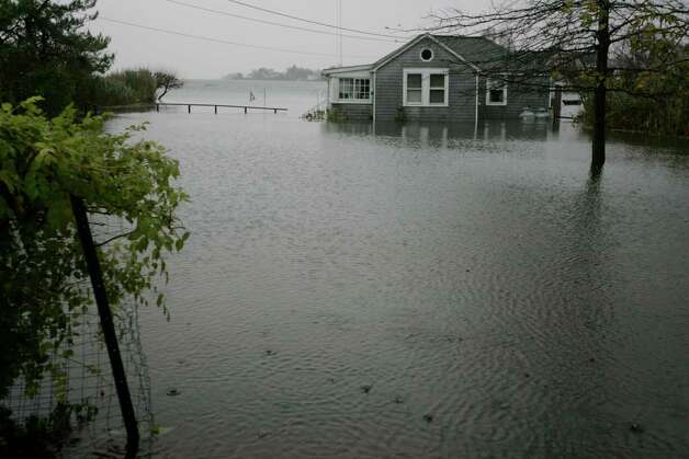 A cottage on Nawthorne Rd in Old Greenwich, Conn. is surrounded by water as Hurricane Sandy entered the area Monday, Oct. 29, 2012. Many of the shoreline communities have been evacuated as the midnight high tide will bring more flooding and storm surge. Photo: J. Gregory Raymond