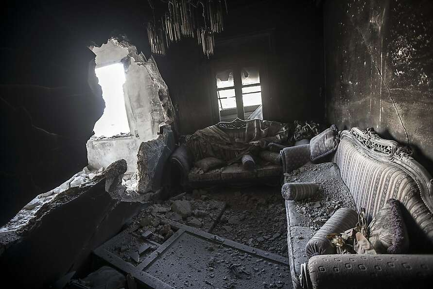 Rubble litters an apartment destroyed by tank shelling in the Karm al-Jabel neighborhood of Aleppo,