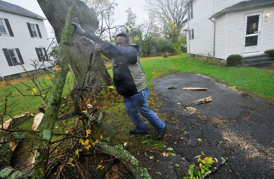 Danbury Highway Department worker Josh Newsome Jr. clears debris from the driveway of Cheryl Rigney, right, after a tree limb fell on Rigney's driveway and across Golden Hill Road during Hurricane Sandy's arrival in Danbury on Monday, Oct. 29, 2012. Photo: Jason Rearick