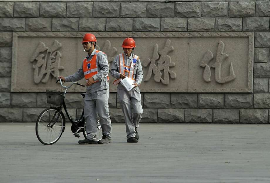 Workers pass by the Sinopec Zhenhai petrochemical factory in Ningbo, China, where protesters concerned about health risks successfully blocked a plan to expand the plant. Photo: Ng Han Guan, Associated Press