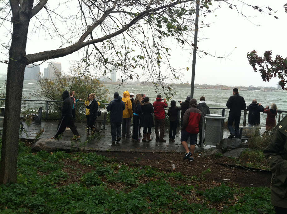 People gather along a choppy East River in Manhattan, New York Monday morning. (Lidia Ryan)