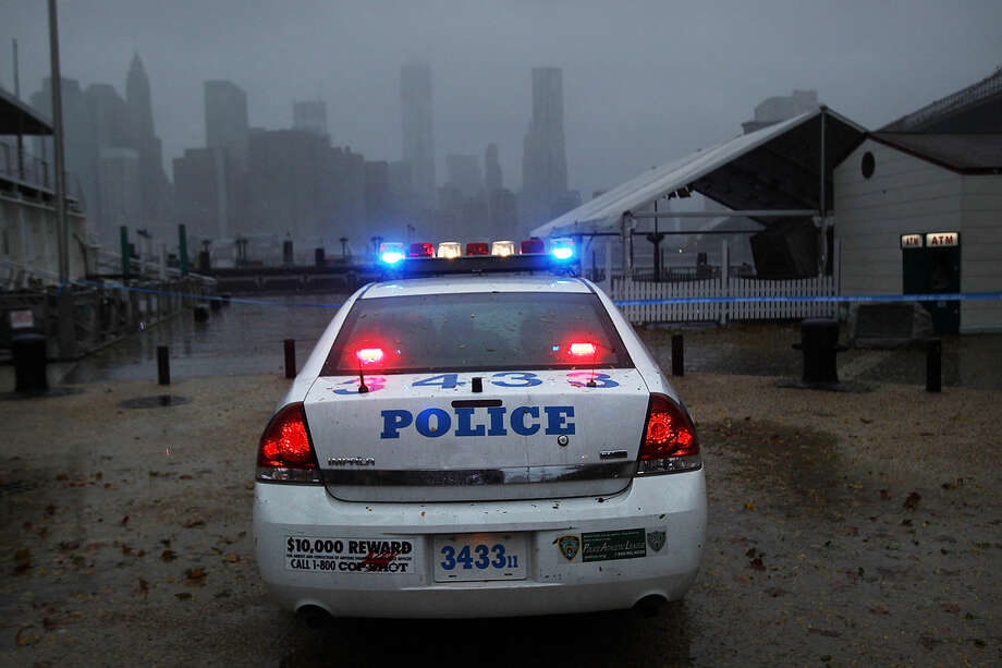 A police car looks out over Manhattan from near the Brooklyn Bridge as Hurricane Sandy begins to affect the area on October 29, 2012 in the in Brooklyn of New York City. The storm, which threatens 50 million people in the eastern third of the U.S., is expected to bring days of rain, high winds and possibly heavy snow. New York Governor Andrew Cuomo announced the closure of all New York City bus, subway and commuter rail service as of Sunday evening. Photo: Spencer Platt, Getty Images / 2012 Getty Images