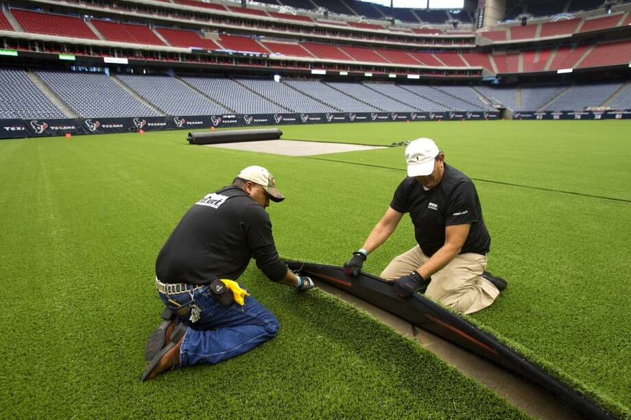 "AstroTurf employees remove the synthetic grass as it's removed from Reliant Stadium. ""We're trying to save the natural grass field for the NFL so it will stay in better condition, and yet we're trying to generate new revenue, "" said Mark Miller, general manager of SMG-Reliant Park. (Cody Duty / Houston Chronicle)"