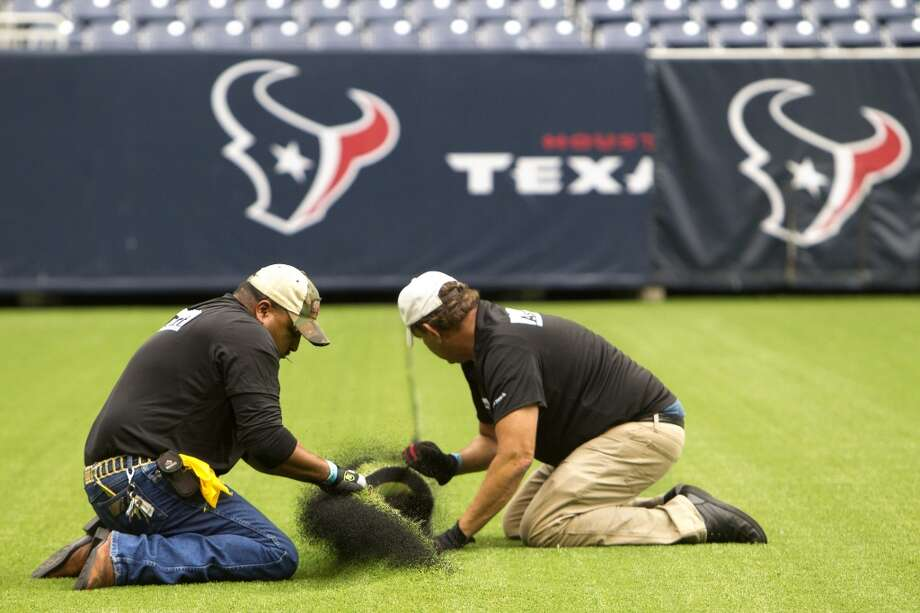 AstroTurf employees Fransisco Lares, left, and Chris Garcia, right, pull up the synthetic grass as it's removed from Reliant Stadium. (Cody Duty / Houston Chronicle)